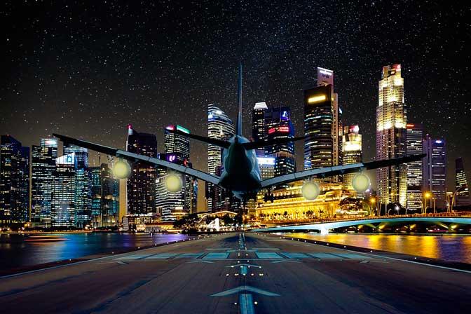 cidade iluminada a noite aviao pousando